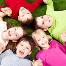 Image of smiling young boys and girls playing on the grass blog people