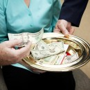 Church members putting money in the collection plate.