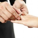 The groom inserting a diamond ring into the bride